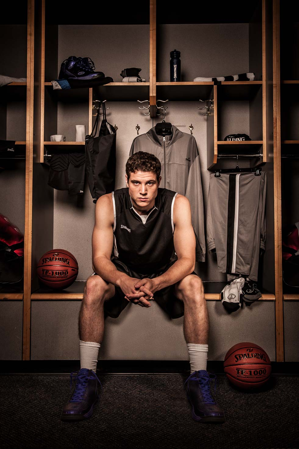 Jimmer Fredette seated in a basketball locker room giving his game face